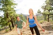 People on hike - couple hiking in forest holding hands. Romantic hikers enjoying trek in beautiful m