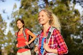Active women - hiking girls walking in forest living healthy lifestyle doing outdoor activities. Female hikers trekking outside in woods wearing backpacks. Portrait of beautiful young blond hiker.