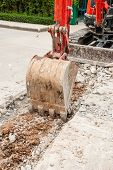 stock photo of excavator  - Excavator breaking concrete road surface. Shows part of the excavator bucket.