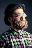 stock photo of bowler  - Strange young man with a beard of flowers wearing elegant bowler hat and glasses - JPG
