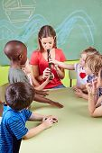 Nursery teacher playing flute for children in a kindergarten