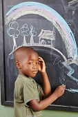 African boy drawing colorful picture on a blackboard in kindergarten