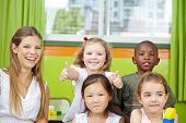 Happy girl in kindergarten group with teacher holding her thumbs up