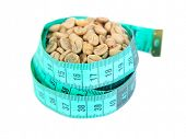 Raw green coffee beans and measuring tape, isolated on white. Concept of weight loss