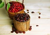 Fresh and dry cranberry in baskets on wooden table