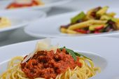 Italian spaghetti topped with bolognaise, or bolognese, sauce with tomatoes, meat and cheese on a pl