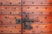 Old red wooden door with metal lock and bolt.