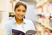 gorgeous indian college girl reading a book in library