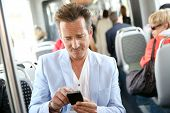 Mature man using smartphone in streetcar