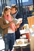 Loving couple walking by book fair on week-end