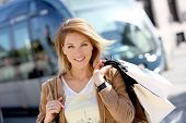 Cheerful woman with shopping bags in town