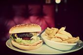 Tasty hamburger and french fries on plate in american food restaurant. Red leather sofa in the background. Vintage, retro style
