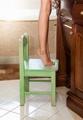 Little Girl Standing On Tiptoes On Chair At Bathroom