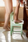 Girl Standing On Wooden Chair At Bathroom Next To Mother