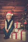 Little boy with gift box under christmas tree in wooden house interior