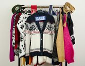 Cute winter sweaters displayed on hangers with a big sale sign.