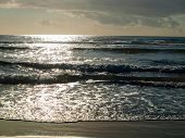 Ocean Waves Breaking On The Beach As The Sun Is Going Down