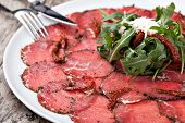 white dish with carpaccio of beef on arugula