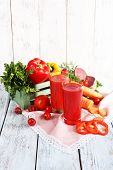 Vegetable juice and fresh vegetables on napkin on wooden table on wooden wall background