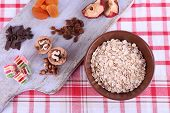Bowl of oatmeal, mug of yogurt, marmalade, chocolate, raisins, dried apricots and walnuts on wooden cutting board on checkered fabric background