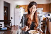 asian teen girl with smartphone in kitchen eating breakfast cereal