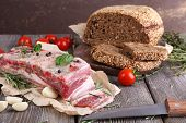 raw bacon with bread and spices on wooden table