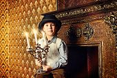 Cute boy in formal suit and bowler hat stands by the fireplace in the room with vintage interior.