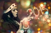 Beautiful young woman in the Santa costume blowing snowflakes and make New Year numbers 2015 on the colorful bokeh background