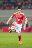 KLAGENFURT, AUSTRIA - MARCH 05, 2014: Zlatko Junuzovic (#10 Austria) kicks the ball in a friendly soccer game between Austria and Uruguay.