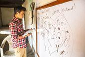 KATHMANDU, NEPAL - DEC 9, 2013: Unknown teacher in lesson at Jagadguru School. School established at 2013, to let new generation learn Sanskrit and preserve Hindu culture.