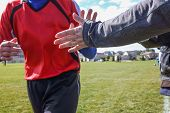 High Five line after a child's soccer game. Some motion blur, focus on arm