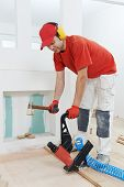 carpenter worker installing wood floor parquet board during flooring work with hammer