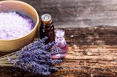 stock photo of massage oil  - Spa still life with lavender oil salt and flowers on wooden table - JPG