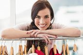 Smiling brunette smiling at camera by clothes rail at clothes store