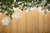 Christmas background with fresh fir-tree, decorative snowflakes and cones on wood with bright snow