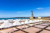 stock photo of salt mines  - salt piles in the saline of Janubio in Lanzarote with old toteen wind mill under blue sky - JPG