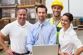 stock photo of warehouse  - Warehouse managers and worker smiling at camera in a large warehouse - JPG