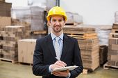 picture of warehouse  - Smiling warehouse manager writing on clipboard in warehouse - JPG
