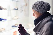 picture of boutique  - Casualy winter dressed lady window shopping in front of sinfully expensive boutique store dispaly window - JPG