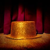 picture of stage theater  - a golden top hat on a stage with the theater curtain in the background - JPG