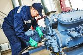 image of manufacturing  - service engineer worker at industrial compressor refrigeration station repairing and adjusting equipment at manufacturing factory - JPG