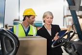 picture of forklift  - Warehouse manager talking with forklift driver in a large warehouse - JPG