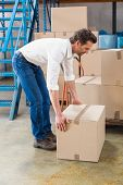 picture of pick up  - Warehouse manager picking up cardboard box in a large warehouse - JPG