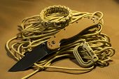 stock photo of paracord  - Folding knife on paracord with paracord bracelet and plastic carabineer - JPG