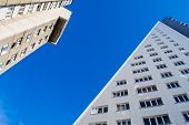 image of penetration  - Traingle shaped apartments penetrate into the clean blue urban sky - JPG