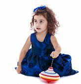 image of dreidel  - cute little girl sitting on the floor and playing dreidel  - JPG