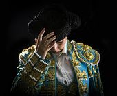 picture of bullfighting  - Woman bullfighter salutes with his montera in black background - JPG