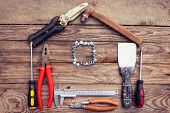 picture of tool  - Construction tools in the form of house on wooden background - JPG