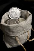 stock photo of sack dollar  - Old silver dollar of USA isolated on black - JPG