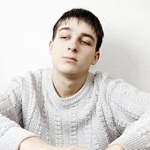 stock photo of pity  - Toned Photo of Pensive Young Man Portrait at the Home - JPG